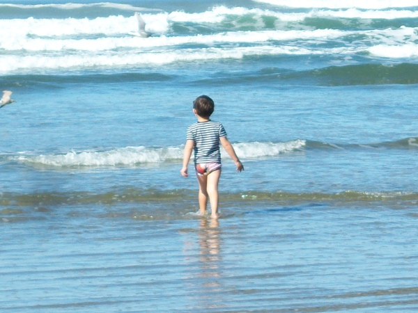 Little boy enjoying the waves on a 77 degree day on October 18, 2011 at Newport, OR beach